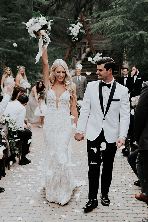rancho-las-lomas-real-wedding-bride-and-groom-walking-down-the-aisle-the-bride-in-a-lace-white-gown-with-a-straps-and-a-deep-v-neckline-the-groom-in-a-white-shawl-lapel-tuxedo-with-black-pants-and-a-black-bow-tie