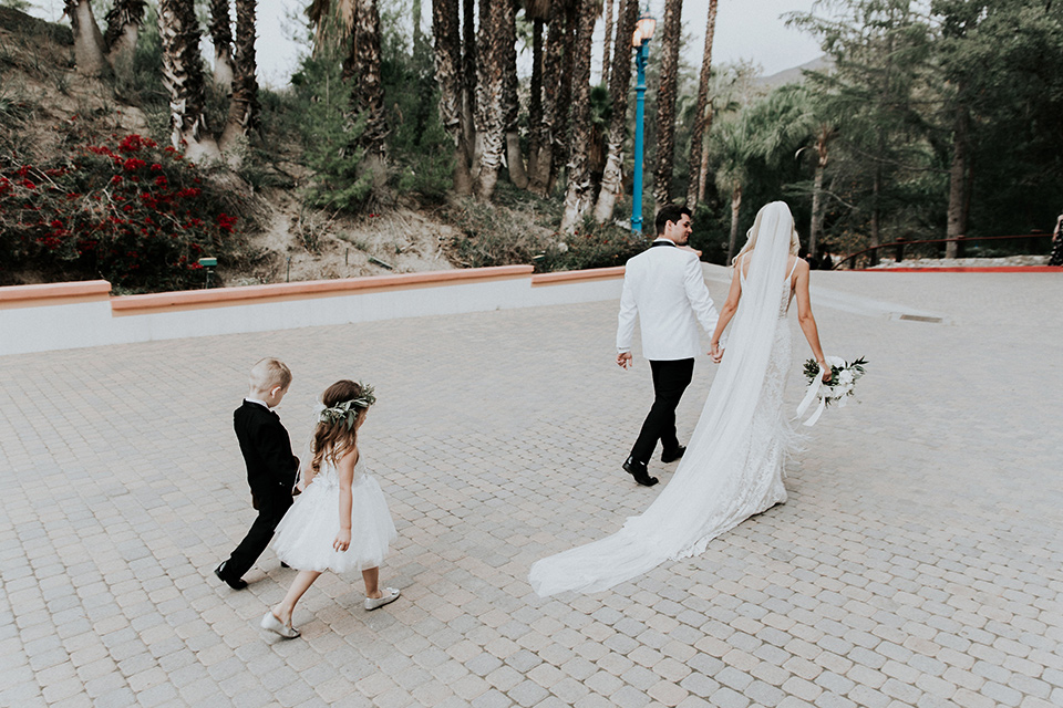 rancho-las-lomas-real-wedding-bride-and-groom-walking-with-children-the-bride-is-in-a-lace-long-gown-with-a-deep-v-and-straps-and-the-groom-is-in-a-white-shawl-lapel-tuxedo-with-black-pants-and-a-black-bow-tie