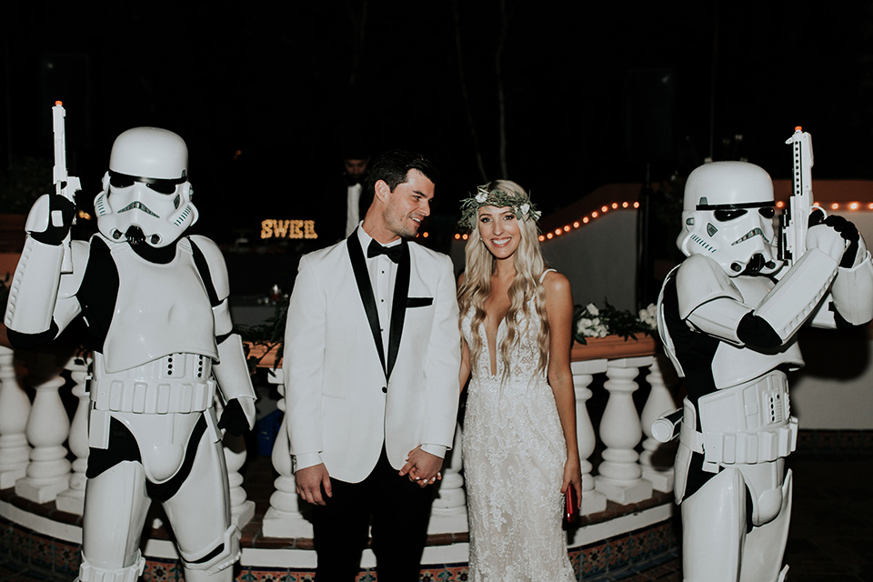 rancho-las-lomas-real-wedding-bride-and-groom-with-stormtroopers-the-bride-is-in-a-lace-long-gown-with-a-deep-v-and-straps-and-the-groom-is-in-a-white-shawl-lapel-tuxedo-with-black-pants-and-a-black-bow-tie