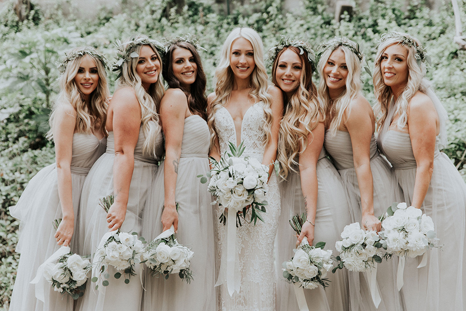 rancho-las-lomas-real-wedding-bridesmaids-close-the-bride-is-in-a-lace-long-gown-with-a-deep-v-and-straps-and-the-bridesmaids-in-taupe-long-gowns