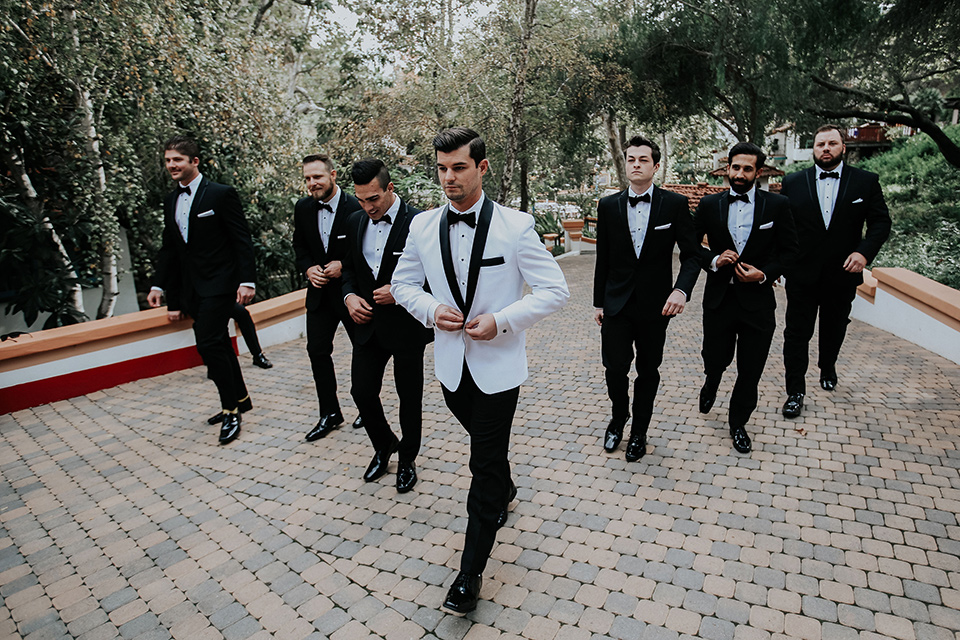 rancho-las-lomas-real-wedding-groom-and-groomsmen-walking-buttoning-jacket-the-groomsmen-in-black-tuxedos-with-black-bow-ties-the-groom-is-in-a-white-shawl-lapel-tuxedo-with-black-pants-and-a-black-bow-tie