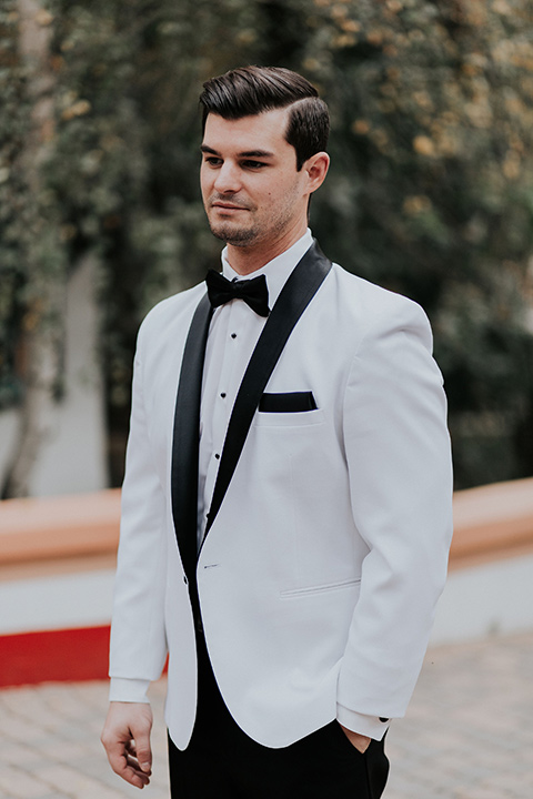 rancho-las-lomas-real-wedding-groom-standing-in-a-white-tuxedo