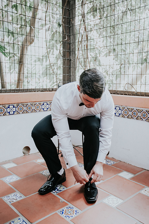 rancho-las-lomas-real-wedding-groom-tying-shoe-in-a-white-shawl-lapel-tuxedo-with-black-pants-and-a-black-bow-tie