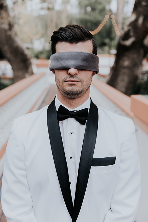 rancho-las-lomas-real-wedding-groom-with-cover-on-eyes-in-a-white-shawl-lapel-tuxedo-with-black-pants-and-a-black-bow-tie