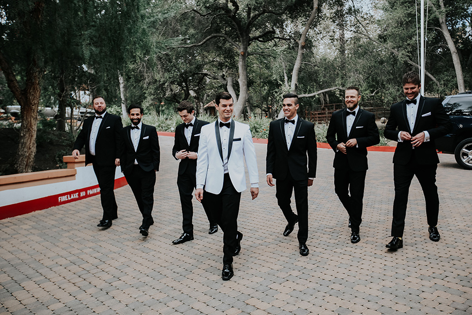 rancho-las-lomas-real-wedding-groomsmen-walking-the-groomsmen-in-black-tuxedos-with-black-bow-ties-the-groom-is-in-a-white-shawl-lapel-tuxedo-with-black-pants-and-a-black-bow-tie