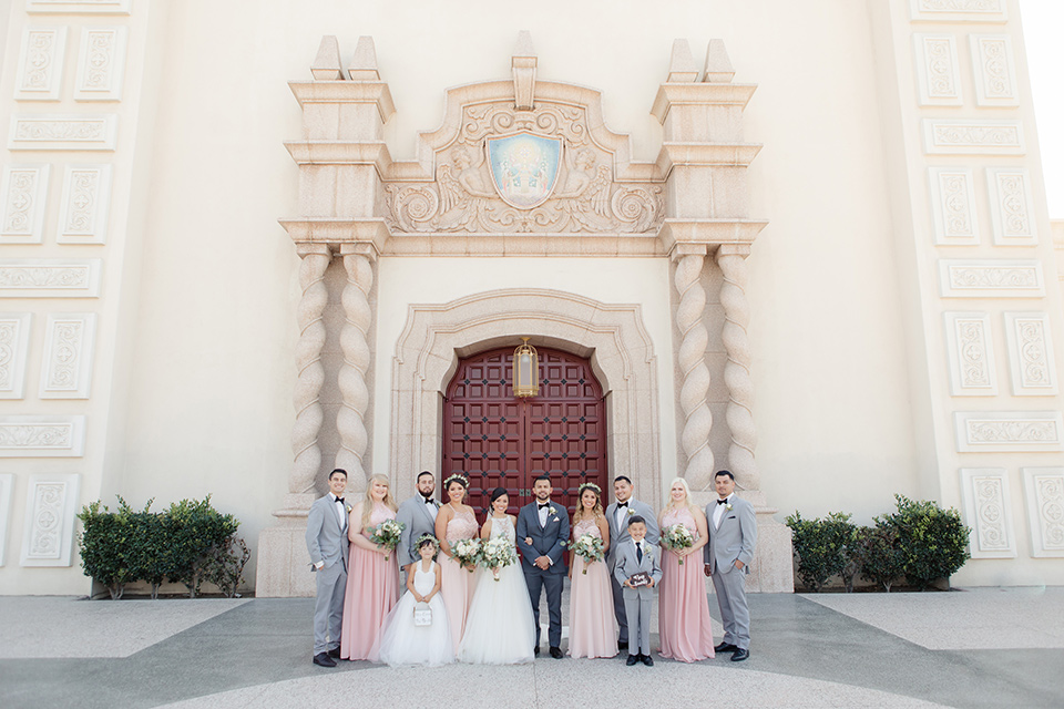 kellogg-house-pomona-wedding-bridal-party-outside-venue-the-bridesmaids-are-in-pink-toned-gowns-the-groomsmen-in-light-grey-suits-bride-in-a-mermaid-style-gown-with-a-high-neckline-and-the-groom-in-a-dark-grey-tuxedo
