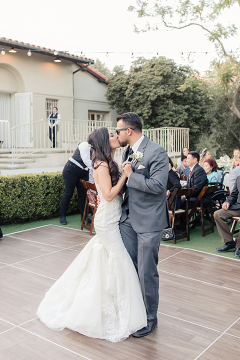 kellogg-house-pomona-wedding-bride-and-groom-dancing-bride-in-a-lace-mermaid-gown-with-a-high-neckline-and-the-groom-in-a-dark-grey-tuxedo-with-a-black-bow-tie