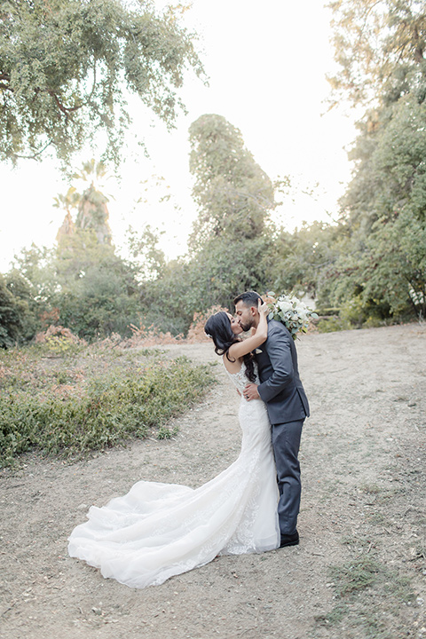 kellogg-house-pomona-wedding-bride-and-groom-kissing-bride-in-a-lace-mermaid-gown-with-a-high-neckline-and-the-groom-in-a-dark-grey-tuxedo-with-a-black-bow-tie