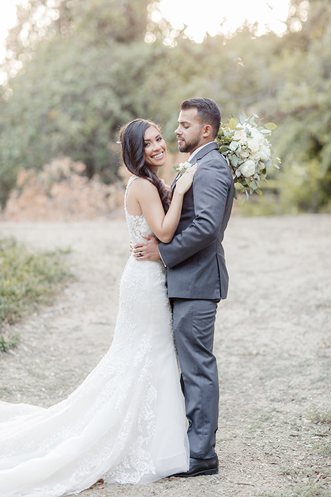 kellogg-house-pomona-wedding-bride-and-groom-looking-at-each-other-bride-in-a-lace-white-gown-with-a-high-neckline-and-a-mermaid-style-skirt-and-the-groom-in-a-dark-grey-tuxedo-with-a-black-bow-tie