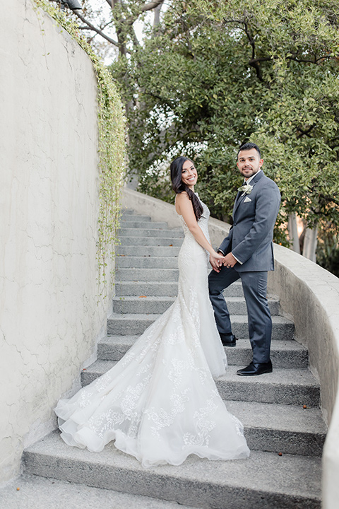 kellogg-house-pomona-wedding-bride-and-groom-on-steps-bride-in-a-lace-white-gown-with-a-high-neckline-and-a-mermaid-style-skirt-and-the-groom-in-a-dark-grey-tuxedo-with-a-black-bow-tie