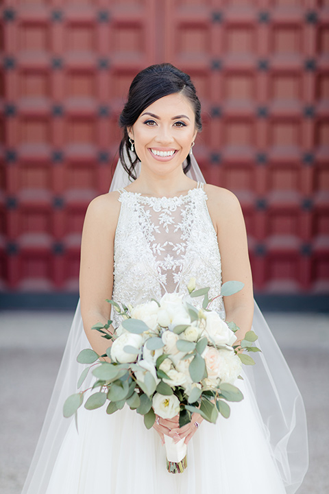 kellogg-house-pomona-wedding-bride-smiling-at-camera-in-a-lace-white-gown-with-a-high-neckline-and-a-mermaid-style-skirt
