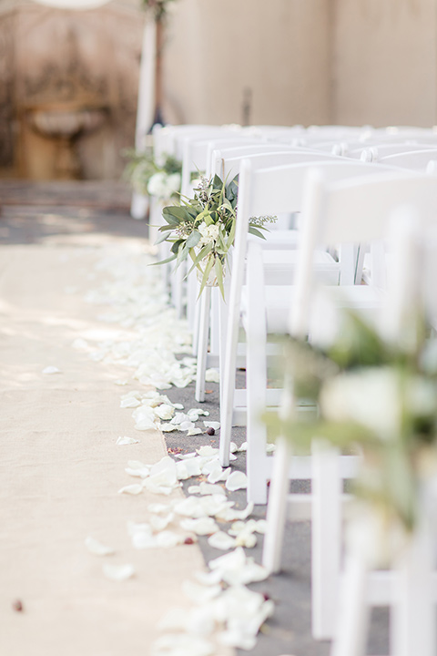 kellogg-house-pomona-wedding-ceremony-chairs-in-white-with-green-simple=florals-hanging-from-them