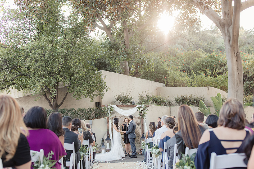 kellogg-house-pomona-wedding-ceremony-with-the-bride-in-a-whtie-lace-gown-and-the-groom-in-a-dark-grey-tuxedo