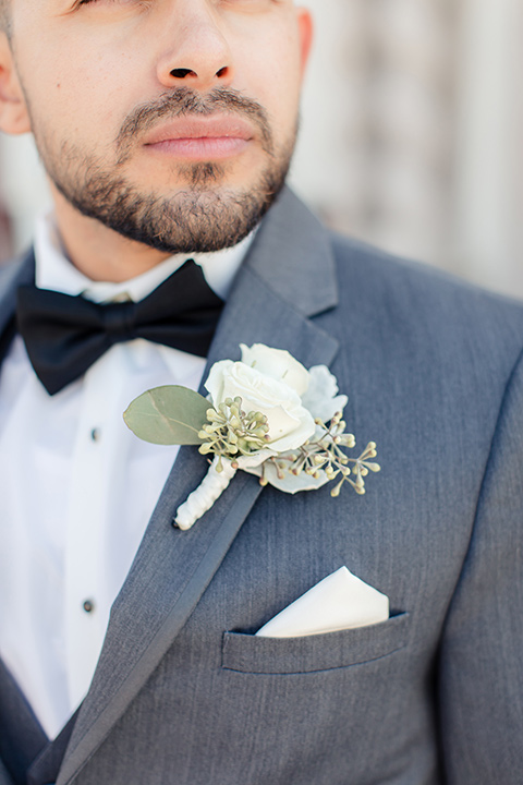 kellogg-house-pomona-wedding-close-up-on-groom-attire-in-a-dark-grey-tuxedo-with-a-black-bow-tie