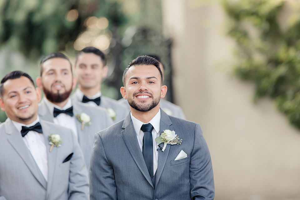 kellogg-house-pomona-wedding-groomsmen-at-ceremony-groomsmen-the-groomsmen-in-light-grey-suits-and-the-groom-in-a-dark-grey-tuxedo