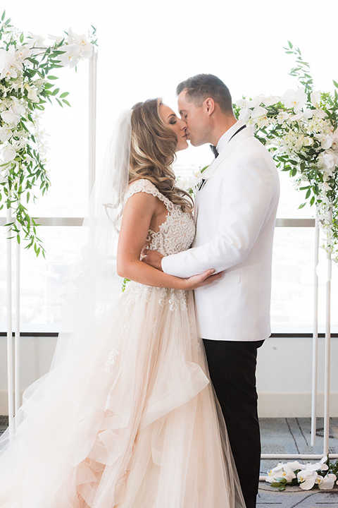 City-club-shoot-bride-and-goom-kiss-bride-in-a-white-ballgown-with-straps-and-a-sweetheart-neckling-groom-in-a-white-coat-with-black-pants