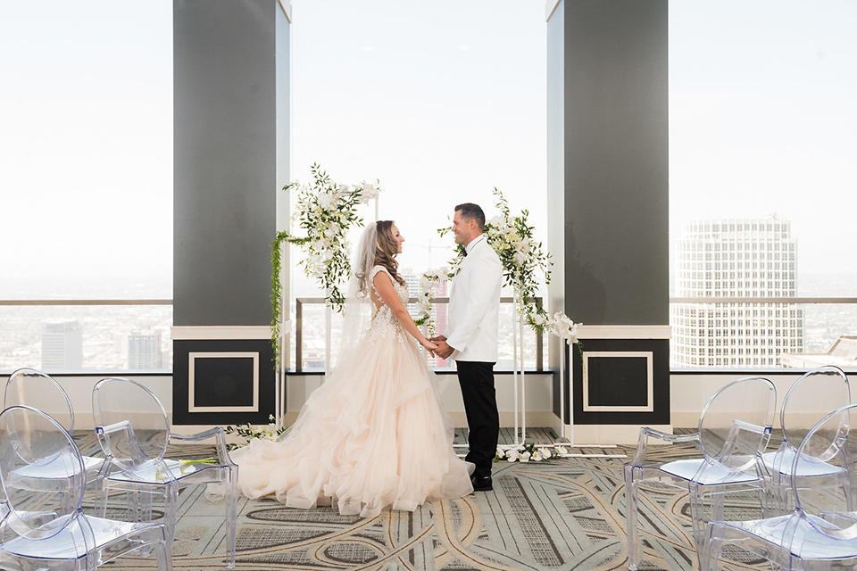 City-club-shoot-bride-and-groom-at-ceremony-bride-in-a-white-ballgown-with-a-sweetheart-neckline-and-straps-groom-in-a-white-coat-with-black-pants