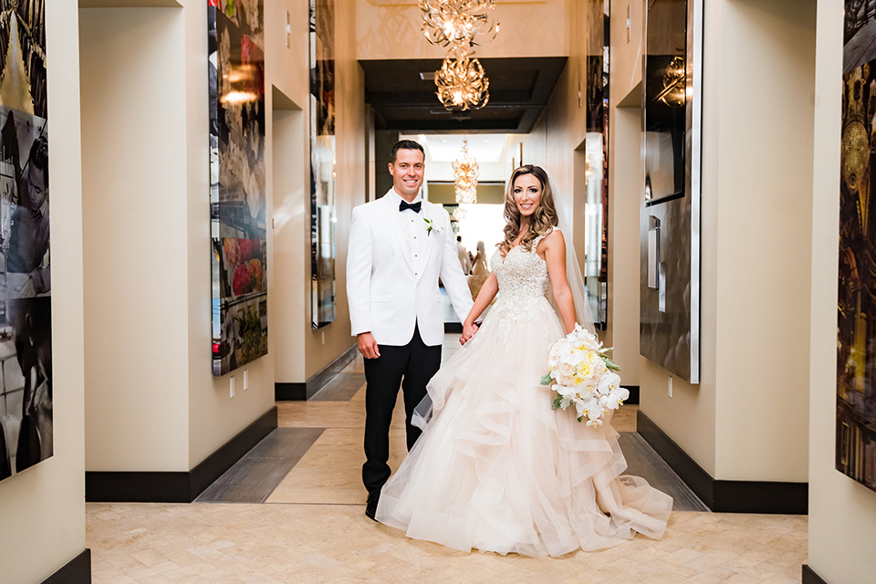 City-club-shoot-bride-and-groom-in-hallway-bride-in-a-white-ballgown-with-a-sweetheart-neckline-and-straps-groom-in-a-white-coat-with-black-pants