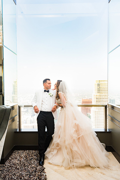City-club-shoot-bride-and-groom-looking-in-different-directions-bride-in-a-white-ballgown-with-a-sweetheart-neckline-groom-in-a-white-jacket-with-black-pants
