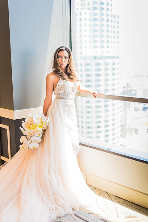 City-club-shoot-bride-looking-at-camera-bride-in-a-white-ballgown-with-straps-and-a-sweetheart-neckling-groom-in-a-white-coat-with-black-pants