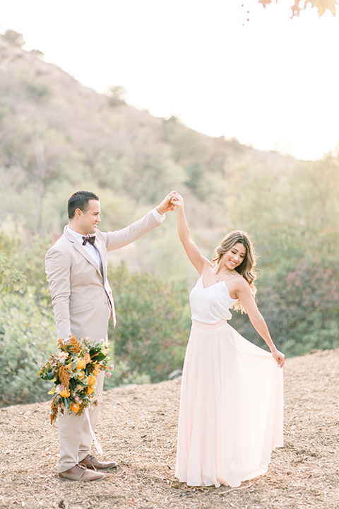 Claudia+Johns-meadow-elopement-bride-and-groom-dancing-bride-in-a-two-toned-gown-with-a-blush-skirt-with-a-white-silk-top-and-the-groom-in-a-tan-suit-with-a-deep-brow-bow-tie