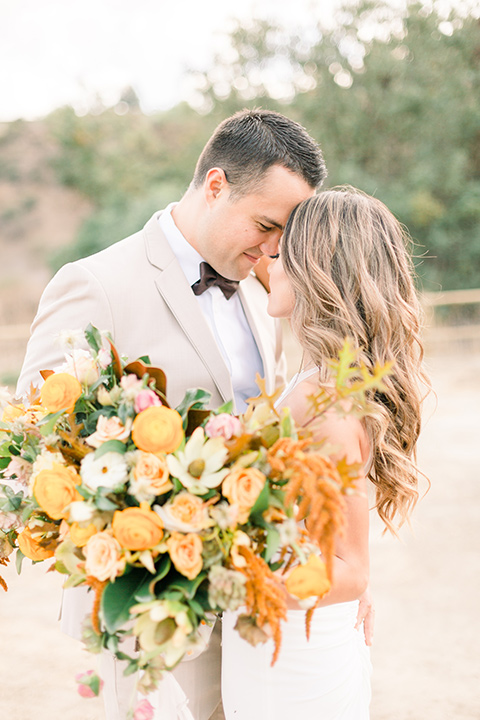 Claudia+Johns-meadow-elopement-bride-and-groom-touching-heads-bride-holding-florals-bride-in-a-two-toned-gown-with-a-light-pink-sjirt-and-a-white-silk-top-the-groom-is-in-a-tan-suit-with-a-deep-brown-bow-tie