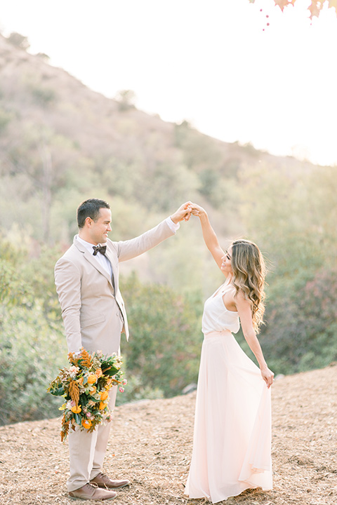 Claudia+Johns-meadow-elopement-bride-and-groom-twirling-bride-in-a-two-toned-gown-with-a-light-pink-sjirt-and-a-white-silk-top-the-groom-is-in-a-tan-suit-with-a-deep-brown-bow-tie