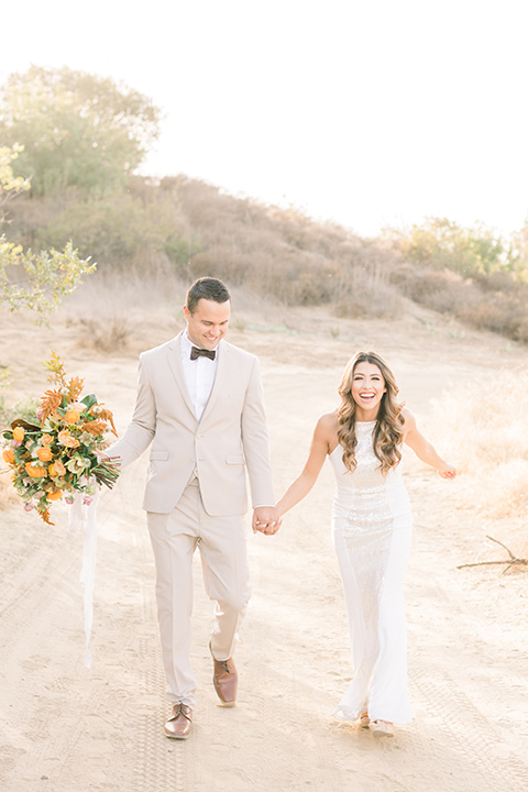 Claudia+Johns-meadow-elopement-bride-and-groom-walking-bride-in-a-two-toned-gown-with-a-light-pink-sjirt-and-a-white-silk-top-the-groom-is-in-a-tan-suit-with-a-deep-brown-bow-tie