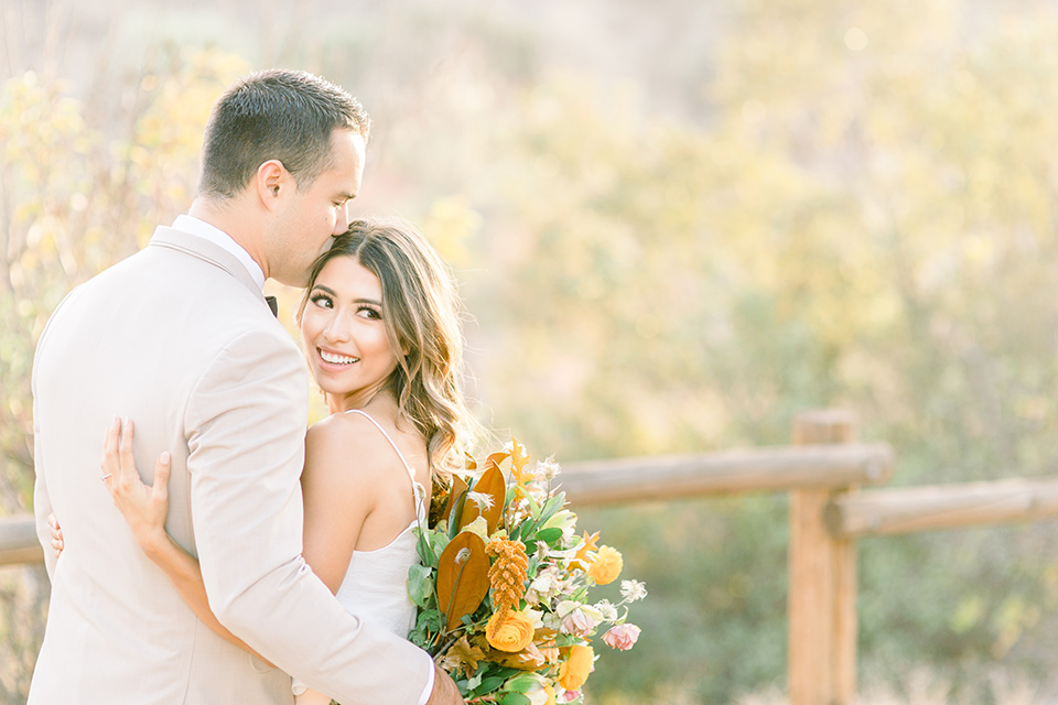 Claudia+Johns-meadow-elopement-bride-looking-at-camera-groom-looking-away-bride-in-a-blush-skirt-and-white-silk-top-the-groom-is-in-a-tan-suit-with-a-brown-bow-tie