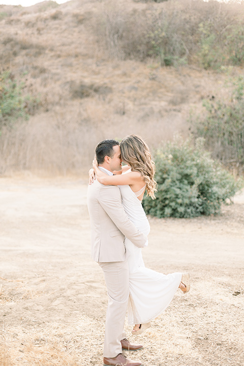 Claudia+Johns-meadow-elopement-groom-holding-up-bride-bride-in-a-two-toned-gown-with-a-blush-skirt-with-a-white-silk-top-and-the-groom-in-a-tan-suit-with-a-deep-brow-bow-tie