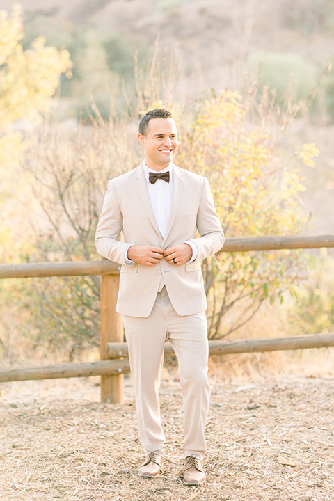 Claudia+Johns-meadow-elopement-groom-groom-is-in-a-tan-suit-with-a-deep-brown-bow-tie