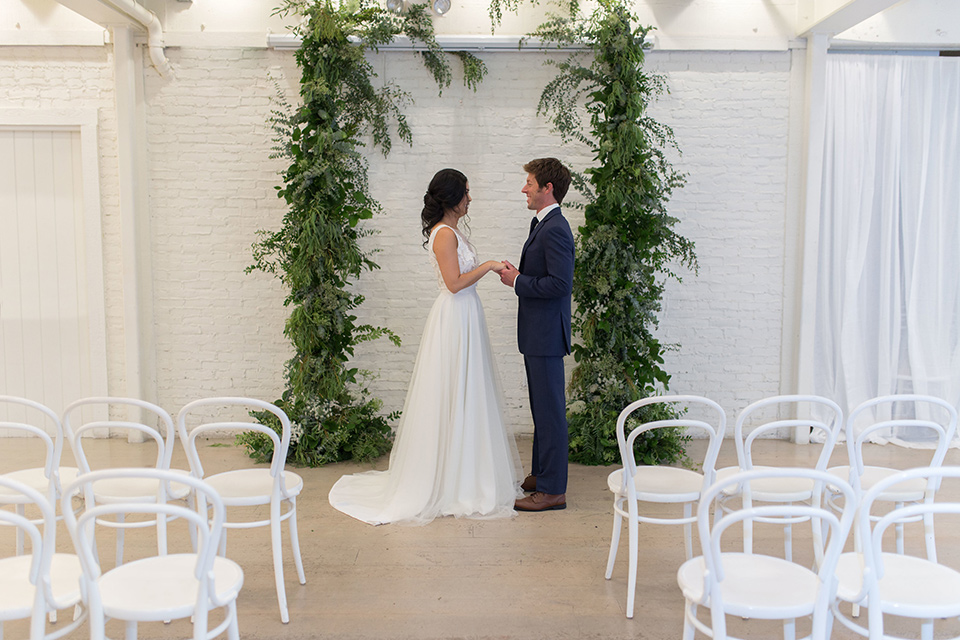 Cooks-Chapel-Shoot-bride-and-groom-at-ceremony-bride-is-in-a-white-flowing-gown-with-a-deep-v-neckline-groom-is-in-a-dark-blue-suit-with-a-navy-long-tie-and-brown-shoes