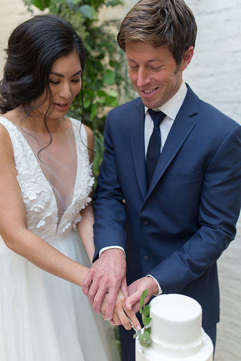 """""""Cooks-Chapel-Shoot-bride-and-groom-cutting-cake-bride-in-a-soft-flowing-gown-with-a-plunging-neckline-while-the-groom-is-in-a-dark-blue-suit-with-a-navy-long-tie-and-brown-shoes"""""""