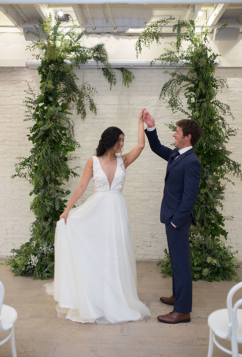 Cooks-Chapel-Shoot-bride-and-groom-dancing-the-bride-is-in-a-white-long-flowing-gown-with-a-deep-v-neckline-while-the-groom-is-in-a-dark-blue-suit-with-a-navy-long-tie