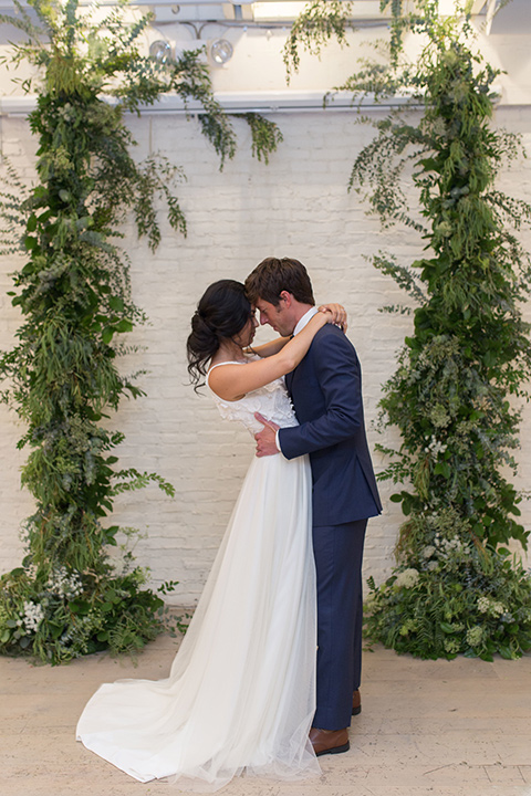 """""""Cooks-Chapel-Shoot-bride-and-groom-facing-each-other-bride-in-a-soft-flowing-gown-with-a-plunging-neckline-while-the-groom-is-in-a-dark-blue-suit-with-a-navy-long-tie-and-brown-shoes"""""""