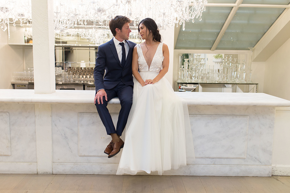 Cooks-Chapel-Shoot-bride-and-groom-on-bar-bride-is-in-a-white-flowing-gown-with-a-deep-v-neckline-groom-is-in-a-dark-blue-suit-with-a-navy-long-tie-and-brown-shoes
