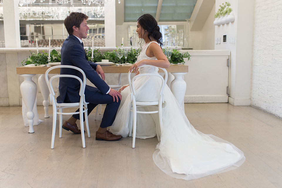 Cooks-Chapel-Shoot-bride-and-groom-sitting-bride-is-in-a-white-flowing-gown-with-a-deep-v-neckline-groom-is-in-a-dark-blue-suit-with-a-navy-long-tie-and-brown-shoes