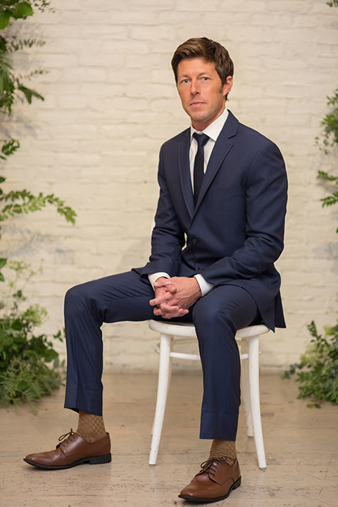 """""""Cooks-Chapel-Shoot-groom-sitting-in-a-dark-blue-suit-with-a-navy-long-tie-and-brown-shoes"""""""