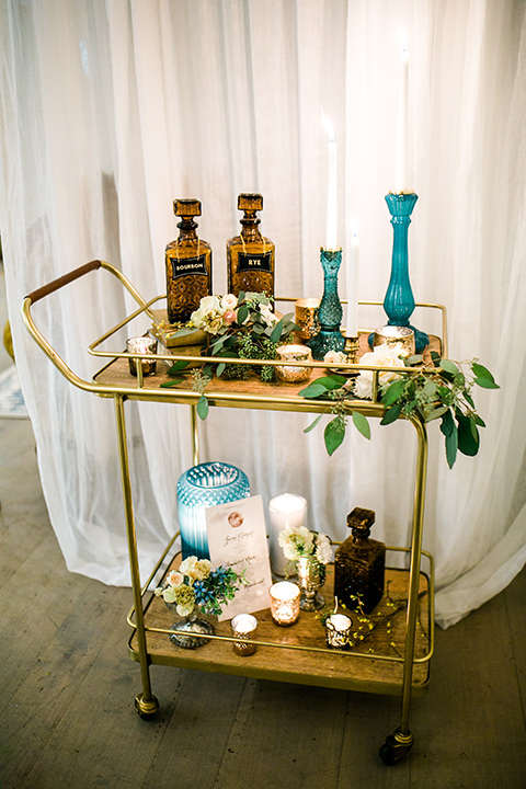 cooks chapel wedding bar cart with florals and candles with light blue stands