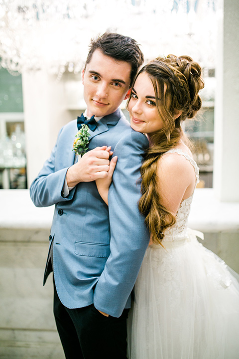Wedding groom hugging the bride in a white ballgown with a lace bodice and straps. The groom is wearing a light blue coat with a dark blue vest in the anaheim packing house