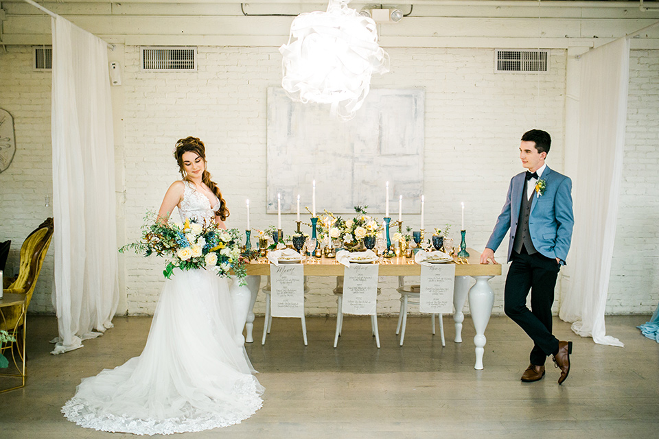Wedding bride and groom on either side of the table with the bride in a white ballgown with a lace bodice and the groom in a light blue coats