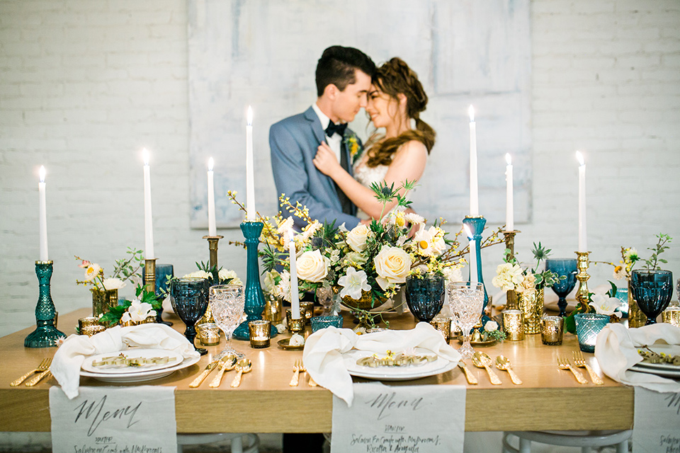 Wedding bride and groom sitting at the table inside Cooks Chapel at the Anaheim packing house decorated with candles and flowers