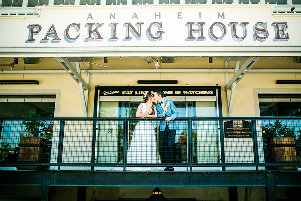 Wedding bride and groom kiss with popsicles in hand outside of the anaheim packing house