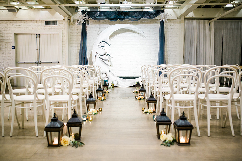 Cooks Chapel Wedding ceremony space with white iron metal chairs and a painted moon arch with black iron lanterns on the floor of the aisle.