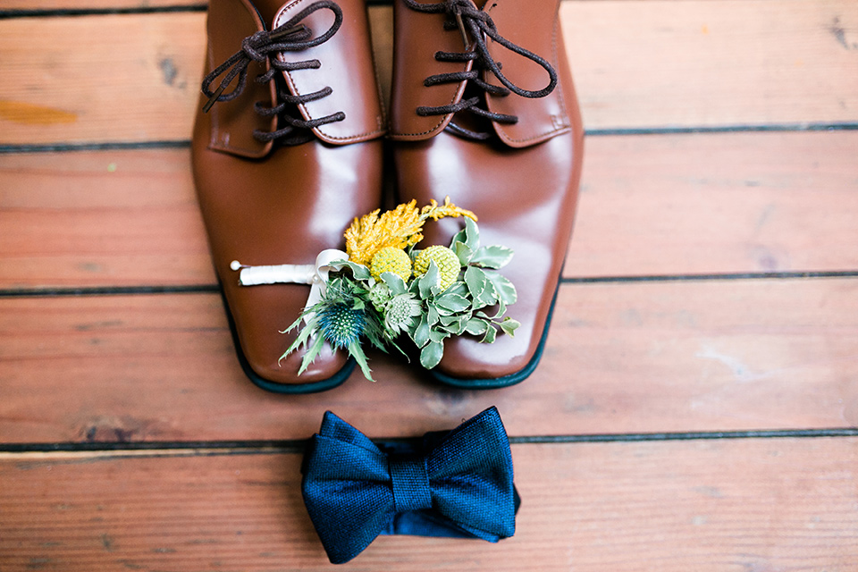 Groom's wedding shoe and accessories and a navy bow tie on top of a wood background
