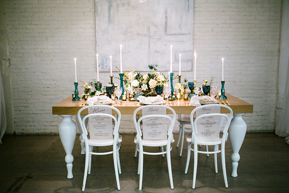 Cooks chapel wedding table set up with a wooden table, florals, candles and white chairs