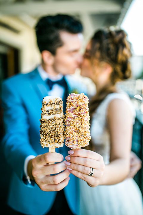 Bride and groom holding popsicles from the anaheim packing house with the bride in a white ballgown and the groom in a light blue suit