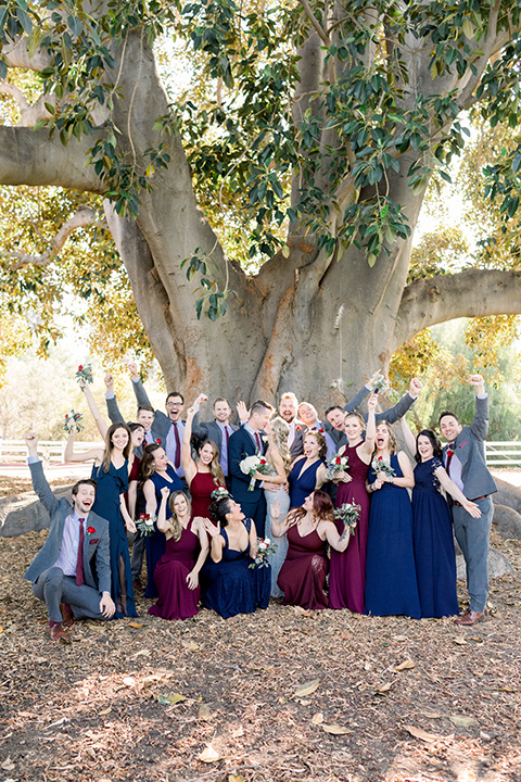red-barn-wedding-bridal-party-hands-in-the-air-bridesmaids-in-alternating-navy-and-burgundy-dresses-groomsmen-in-grey-suits-bride-in-a-lace-fitted-dress-with-thin-straps-groom-in-a-blue-suit-with-grey-vest-and-burgundy-tie