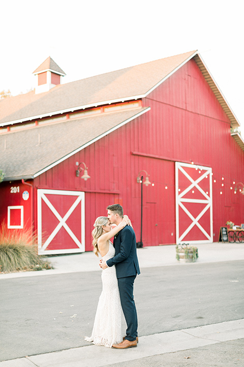 red-barn-wedding-bride-and-groom-in-front-of-barn-bride-in-a-lace-fitted-dress-with-thin-straps-groom-in-a-blue-suit-with-grey-vest-and-burgundy-tie