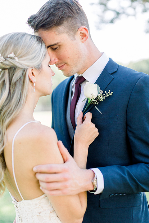 red-barn-wedding-bride-and-groom-heads-touching-close-bride-in-a-lace-fitted-dress-with-thin-straps-groom-in-a-blue-suit-with-grey-vest-and-burgundy-tie